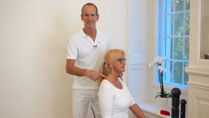 Roland Liebscher steht hinter einer blonden Frau und zeigt auf Ihre Schulter