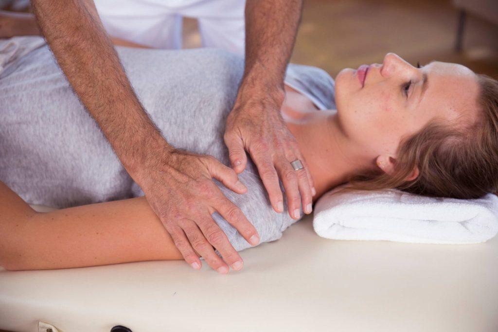 Zwei Männerhände behandeln die linke Schulter einer liegenden Frau