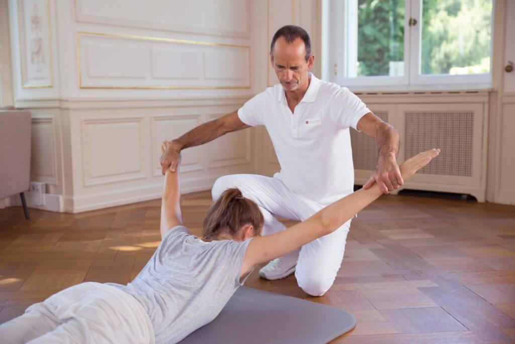 """Eine Frau liegt bäuchlings auf einer Bodenmatte. Roland Liebscher-Bracht kniet vor ihr und zieht ihre Arme """"V""""-förmig über den Kopf hinweg auseinander."""