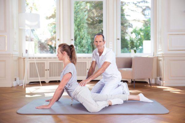 Eine Frau liegt bäuchlings auf einer Bodenmatte, stützt sich mit beiden Armen nach oben ab, ein Bein ist angewinkelt. Roland Liebscher-Bracht legt eine Hand auf ihren unteren Rücken.