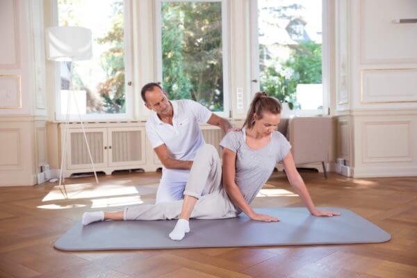Eine Frau liegt seitlich auf einer Bodenmatte und führt mithilfe von Roland Liebscher-Bracht eine Übung aus.
