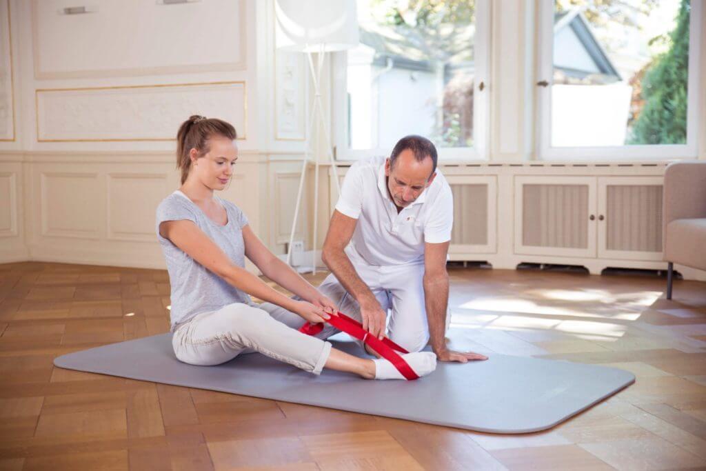 Eine Frau sitzt aufrecht auf einer Bodenmatte, ihre Füße sind in der Übungsschlaufe. Sie sitzt an der Schlaufe, Roland Liebscher-Bracht achtet auf die korrekte Ausführung.