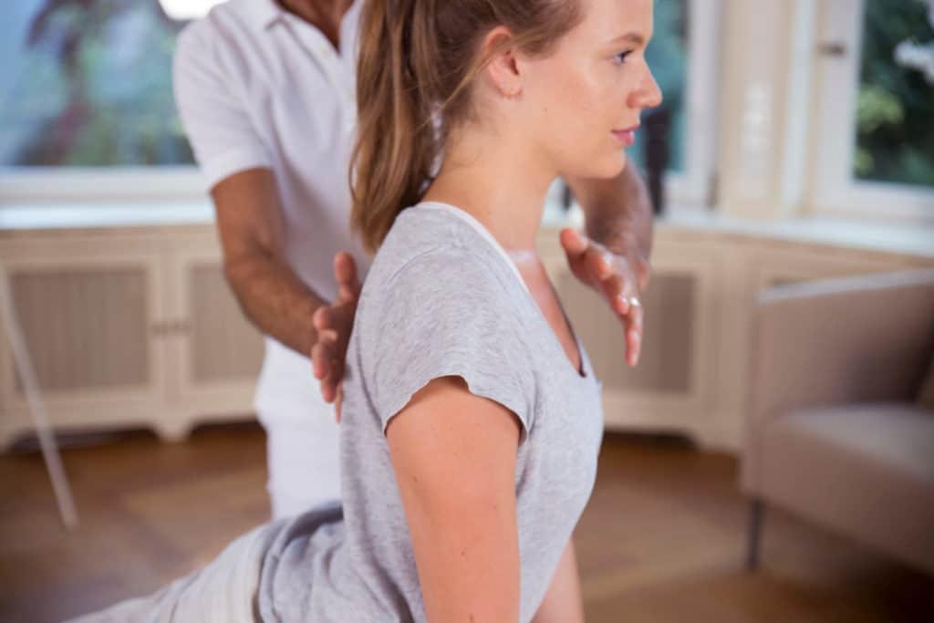Roland Liebscher hält zur Erklärung einer Übung zu Schulterschmerzen die eine Hand vor die obere Brust einer Frau und die andere Hand dahinter