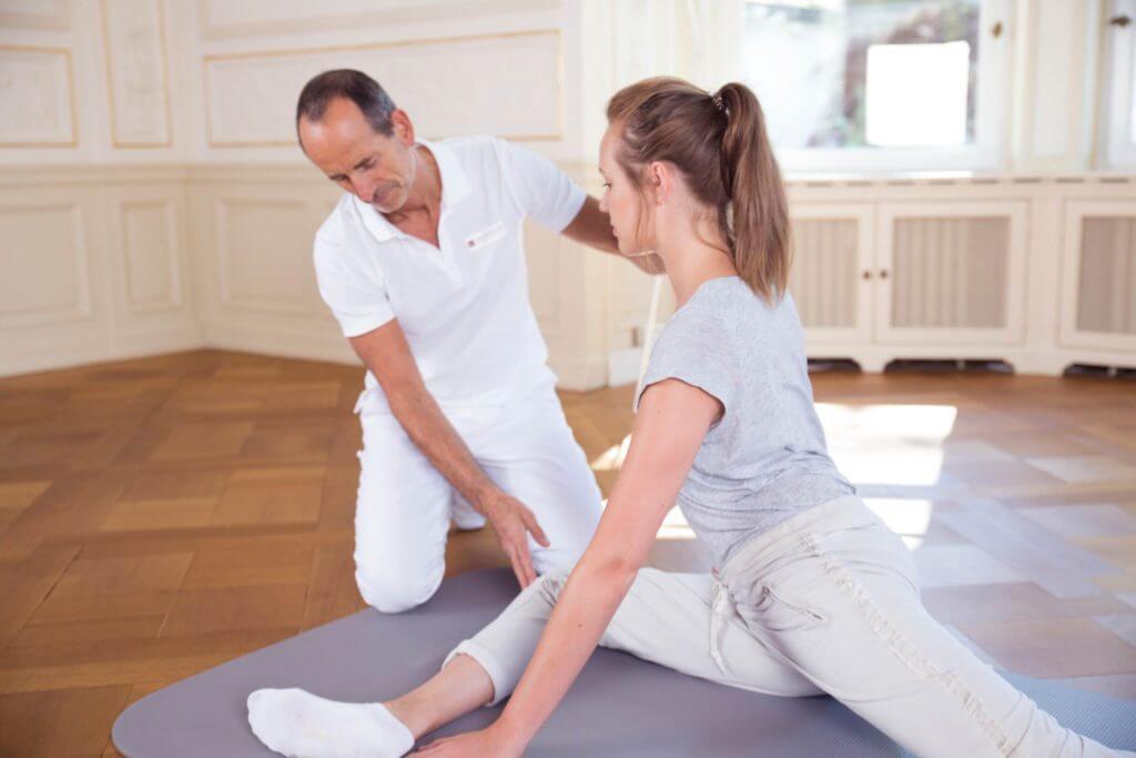 Roland Liebscher-Bracht achtet auf die richtige Ausführung einer Übung. Die Frau liegt auf einer Bodenmatte, hat ein Bein vor sich liegen, das andere hinter sich gestreckt.