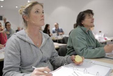 Eine blonde Dame hört aufmerksam zu und ist bereit Notizen von der Schmerztherapie Ausbildung von Liebscher & Bracht zu machen