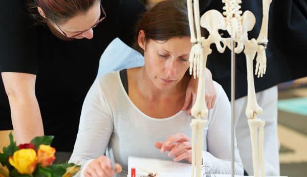 Ein Frau sitzt hinter einem künstlichem Skelett und über dem Heilpraktiker Ausbildungsunterlagen von Liebscher & Bracht. Ein Mann hat seinen linken Arm über ihre Schulter gelegt und hilft ihr dabei.