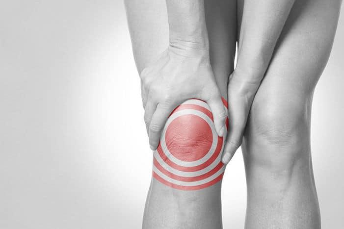 Auf einem schwarz/weiß Bild halten zwei Hände das eigene Knie. Das rechte Knie ist wie bei einer Zielscheibe rot hervorgehoben.