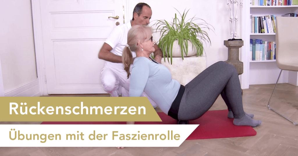 """Roland Liebscher zeigt einer älteren Frau eine Übung mit der FAszienrolle, auf der sie sitzt und links unten steht als Banner """"Rückenschmerzen - Übungen mit der Faszienrolle"""""""