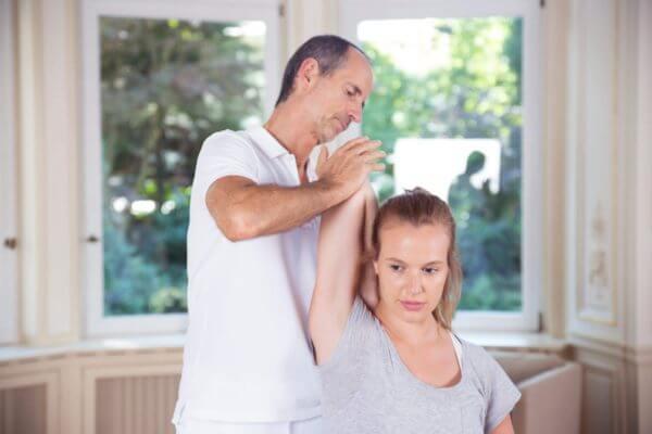 Roland Liebscher-Bracht zeigt einer Frau eine Dehnübung. Dabei zieht er ihren Arm gebeugt hinter ihren Kopf.