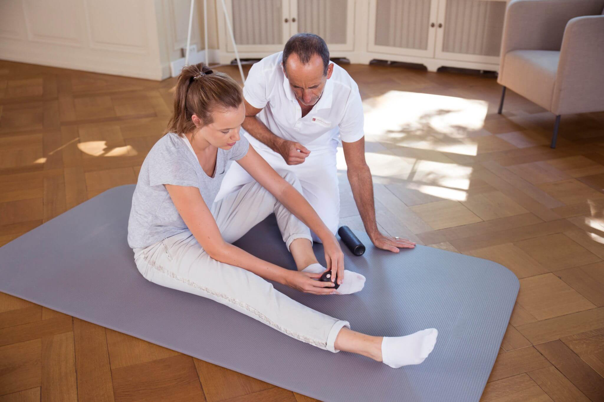 Frau massiert ihren Fuß mit der Minifaszienkugel. Sie sitzt dabei auf einer Bodenmatte. Roland Liebscher-Bracht betrachtet sie.