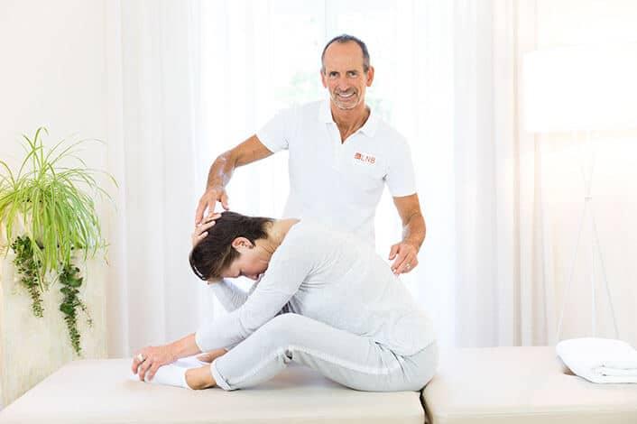 Eine Frau sitzt auf einer Liege und beugt sich zu ihren Füßen. Die Beine liegen nach außen angewinkelt. Roland Liebscher-Bracht achtet auf die korrekte Ausführung.