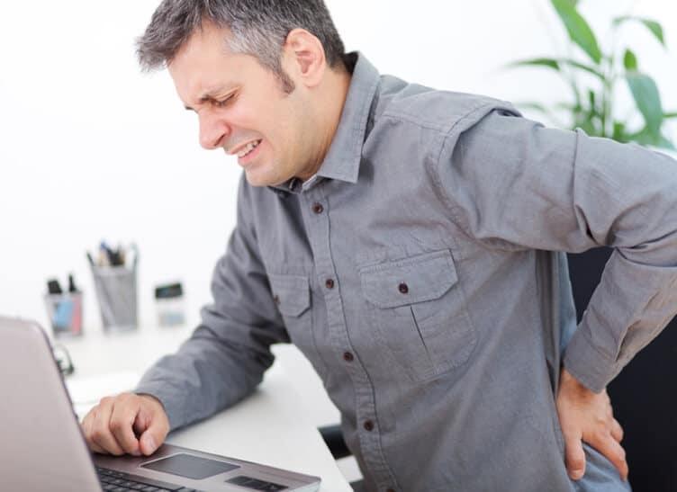 Ein Mann mit schmerzverzerrtem Blick hält sich an seinem Rücken.