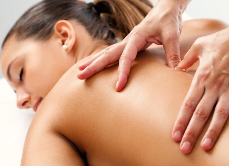 Eine Frau wird am oberen Rücken massiert.