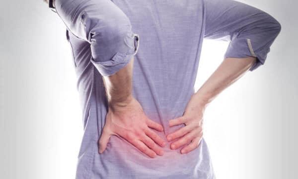 Es ist der Rücken von einem Mann in einem blauen, dünnen Jeans-Hemd vor weißem Hintergrund zu sehen, der sich mit beiden Händen vor Schmerzen den unteren Lendenwirbelbereich hält, welcher rötlich hervorgehoben ist.