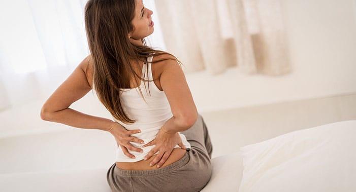 Ein dunkelhaarige Frau, die auf einem Bett sitzt, hält sich mit beiden Armen den unteren Rücken vor Schmerzen