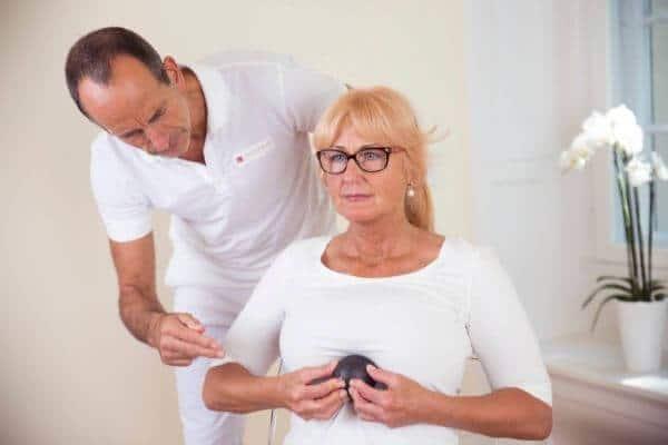 Roland Liebscher-Bracht zeigt einer Frau eine Übung. Sie sitzt aufrecht und massiert den Brustbereich mit der Minifaszienkugel.