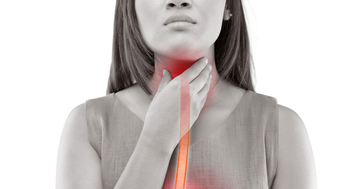 Frau hält sich den von Sodbrennen schmerzenden Hals