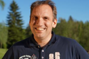 Simon Steeb, seit 25 Jahren Staplerfahrer, lächelt in einem dunkelblauen Polo Shirt in die Kamera