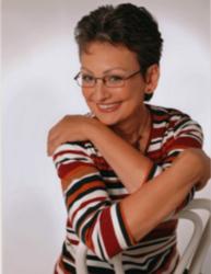 Frau Ilona Frosch sitzt glücklich lächelnd auf einem umgedrehten, weißen Holzstuhl und umarmt sich dabei selbst