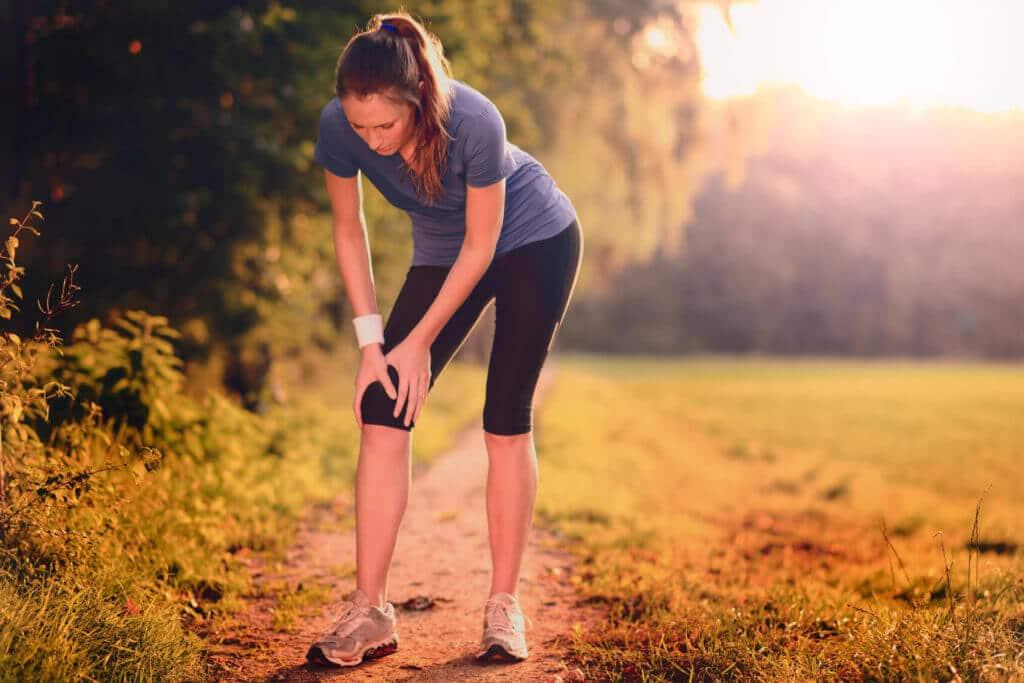 Eine Frau kommt beim Joggen zum Stehen und hält sich nach unten gebeugt das Knie.