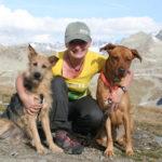 Anke Vogel sitzt zwischen ihren zwei Hunden auf einem Berg. Im Hintergrund sind viele weitere Berge zu sehen.