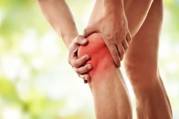 Ein schmerzendes Knie mit Arthrose wird von zwei Händen gehalten