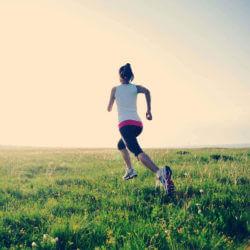 Frau joggt auf Wiese