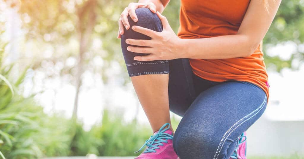 Eine Frau hockt im Freien auf ihrem Knie und hält sich ihr Knie.