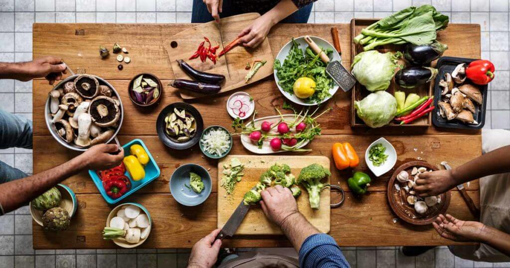 Tisch mit gesundem Essen und Menschen, die es zubereiten