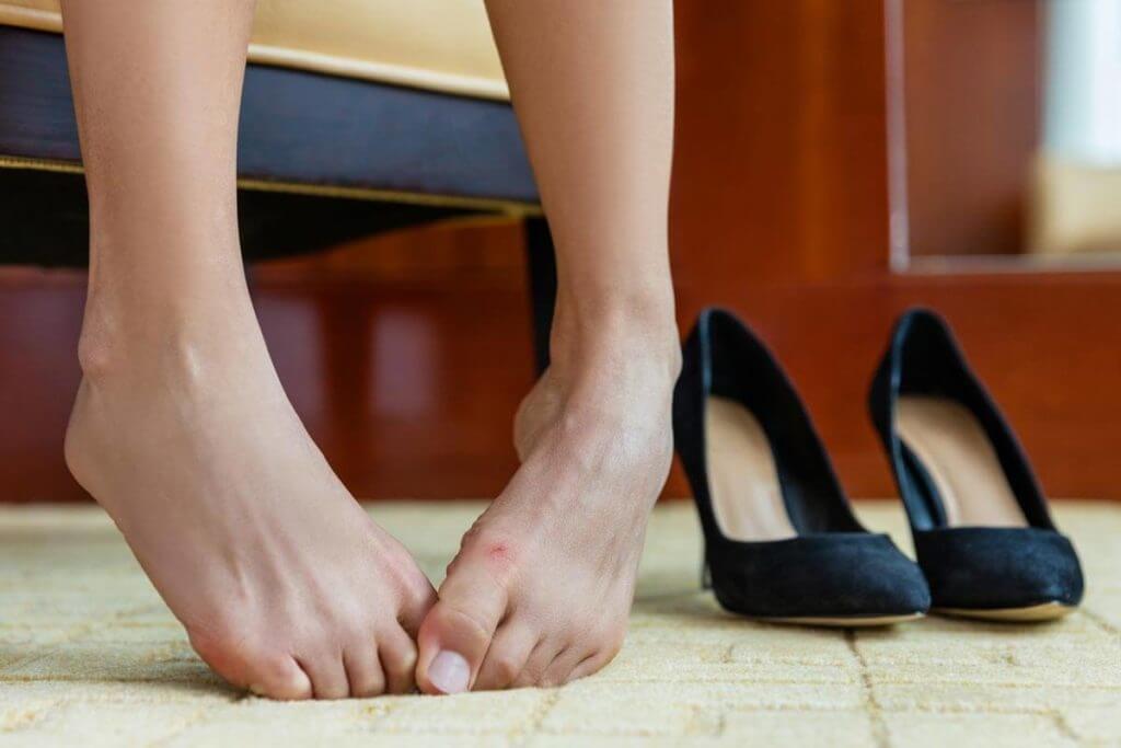 Füße einer Frau neben einem Paar Pumps.