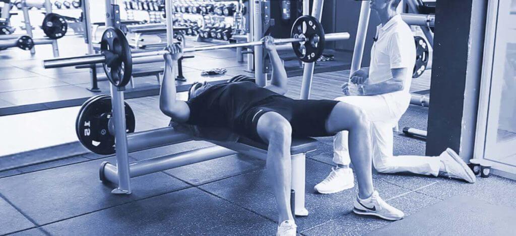 Fitness-Sportler beim Krafttraining und Bankdrücken auf der Hantelbank gegen ISG-Schmerzen