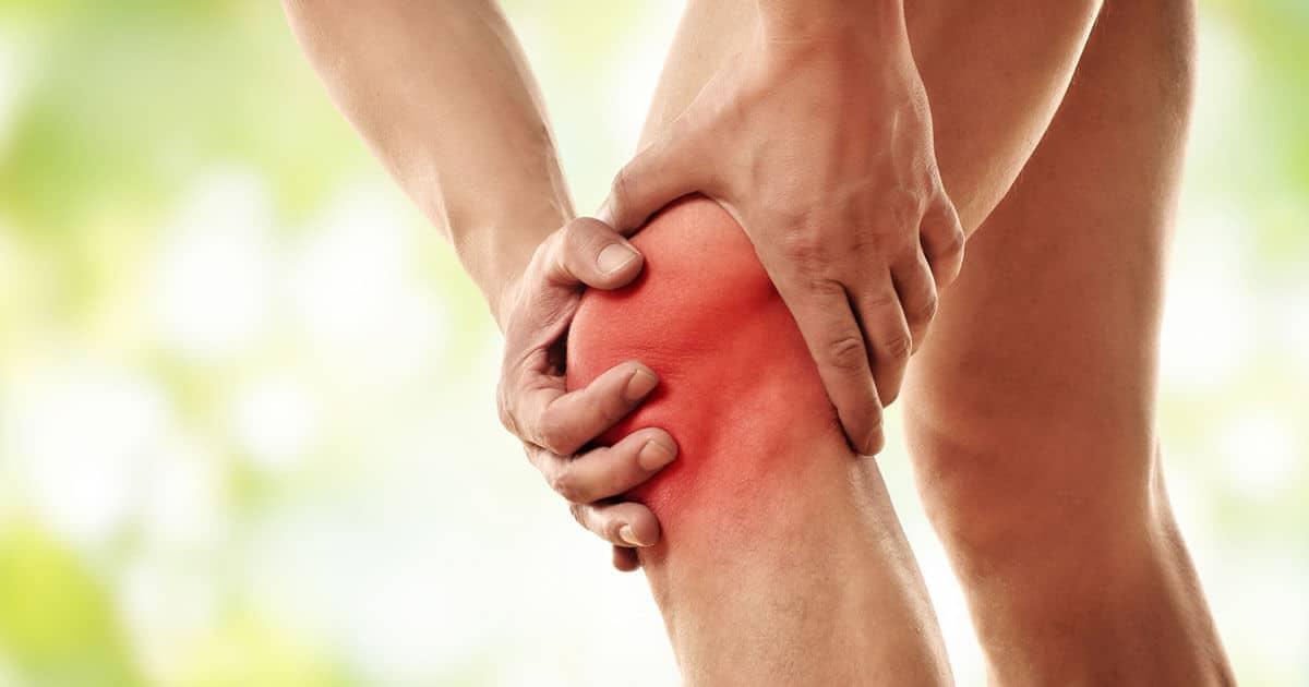 Ein schmerzenden Knie mit Arthrose wird von zwei Händen gehalten