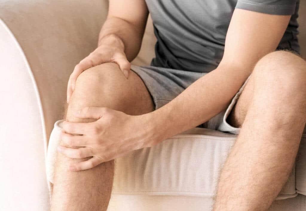 Ein Mann, der unter Schmerzen in der Kniekehle leidet, während er auf dem Sofa sitzt