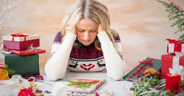 Gestresste Frau an einem Tisch mit Geschenken in der Weihnachtszeit