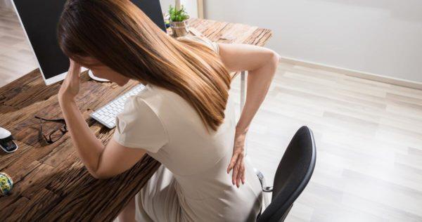 Eine Frau sitzt am Schreibtisch und hält sich vor Schmerzen gekrümmt den unteren Rücken.