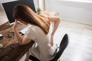 Frau sitzt am Schreibtisch und hält sich den unteren Rücken, der durch die Ischialgie schmerzt