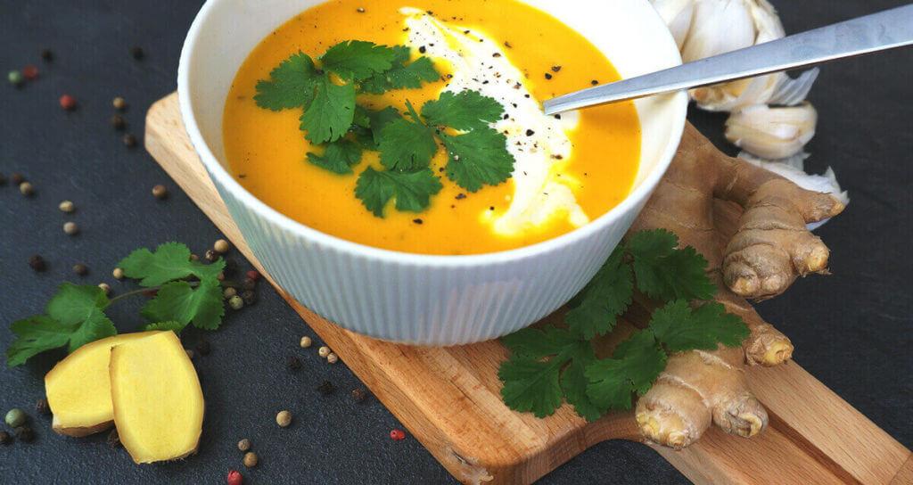 Ingwer-Möhren-Suppe, angerichtet mit Korianderblätter auf einem braunen Holzbrett