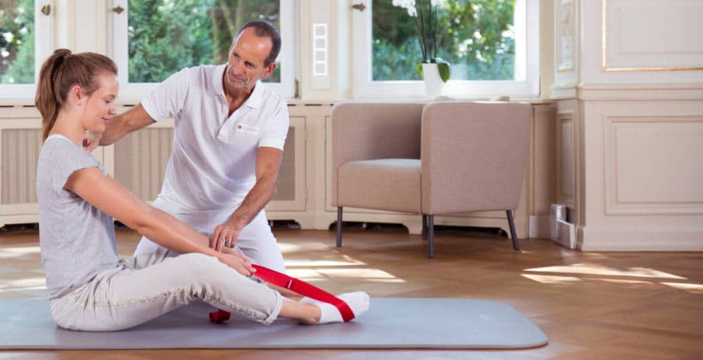 Roland Liebscher-Bracht zeigt einer Schmerzpatienten Übungen gegen Rückenschmerzen