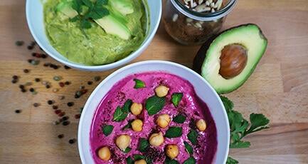 Avocado-Hummus und Rote Beete Hummus in zwei Schalen. Das Rote-Beete-Hummus ist dekoriert mit Kichererbsen und Korianderblättern. Auf dem Avocado-Hummus sind Avocado-Scheiben und Korianderblätter zu sehen.