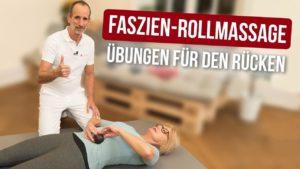 """Eine Frau liegt auf einer Bodenmatte, und massiert ihren Bauchbereich mit einer Faszienkugel. Roland Liebscher-Bracht kniet neben ihr. Über ihnen der Schriftzug """"Drei Faszien-Rollmassagen den Rücken"""""""