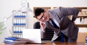 Ein Mann beim Telefonieren hat Gesäßschmerzen im Büro