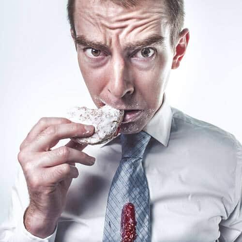 Mann isst und kleckert auf seine Krawatte