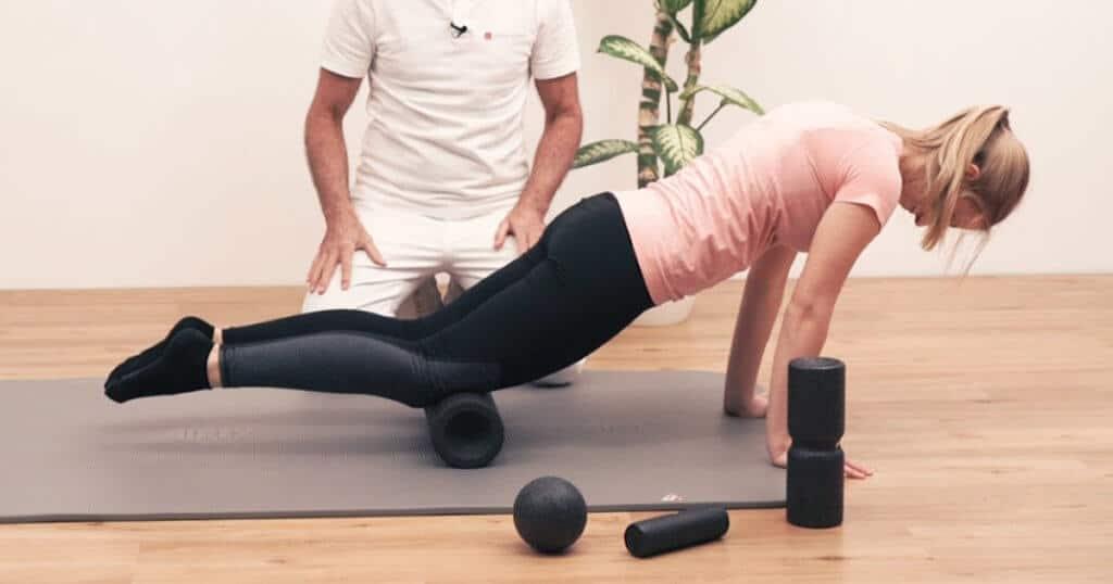 Patientin macht eine Faszien-Rollmassage mit der Maxi-Rolle von Liebscher & Bracht