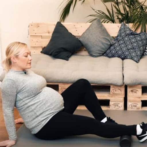 Schwangere Frau bei einer Übung mit einer Faszienrolle gegen Wassereinlagerungen