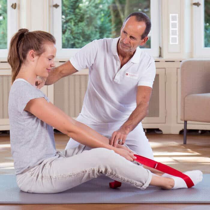Schmerzspezialist Roland Liebscher-Bracht zeigt einer Patientin die Engpassdehnübung