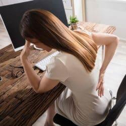 Eine Frau sitzt am Schreibtisch und hält sich mit schmerzverzerrter Körperhaltung den Rücken.