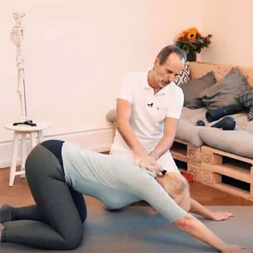 Eine Frau beugt im Vierfüßlerstand den Oberkörper weit nach unten, Roland Liebscher-Bracht hält seine Hände auf ihrem oberen Rücken.
