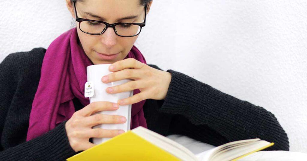 Eine Frau liest ein Buch und trinkt dabei einen Becher Tee.