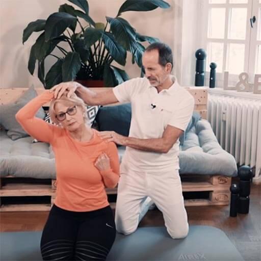 Eine Frau im Knien bei einer seitlichen Dehnung für den Nacken. Sie sieht mit dem rechten Arm ihren Kopf nach rechts, Roland Liebscher-Bracht unterstützt sie dabei.