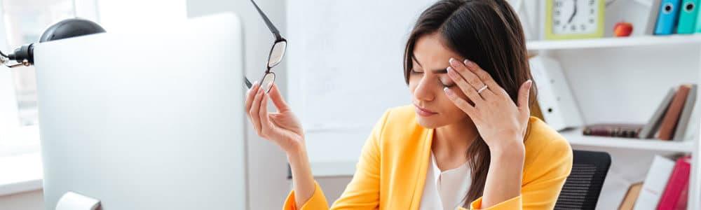 Eine Frau hat Augenschmerzen nach zu langem Arbeiten am Bildschirm im Büro